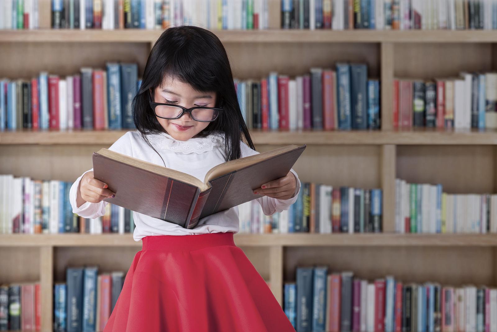 bigstock-schoolgirl-reads-book-in-libra-73221412_overlay1